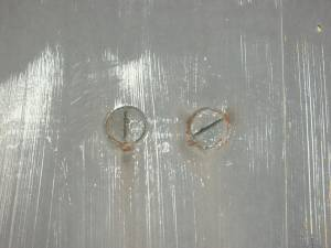 bolts on scratched metal wall