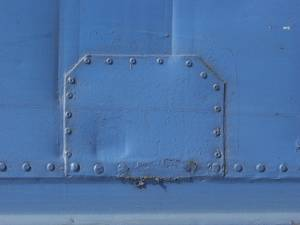 Blue painted metal plate studded with bolts