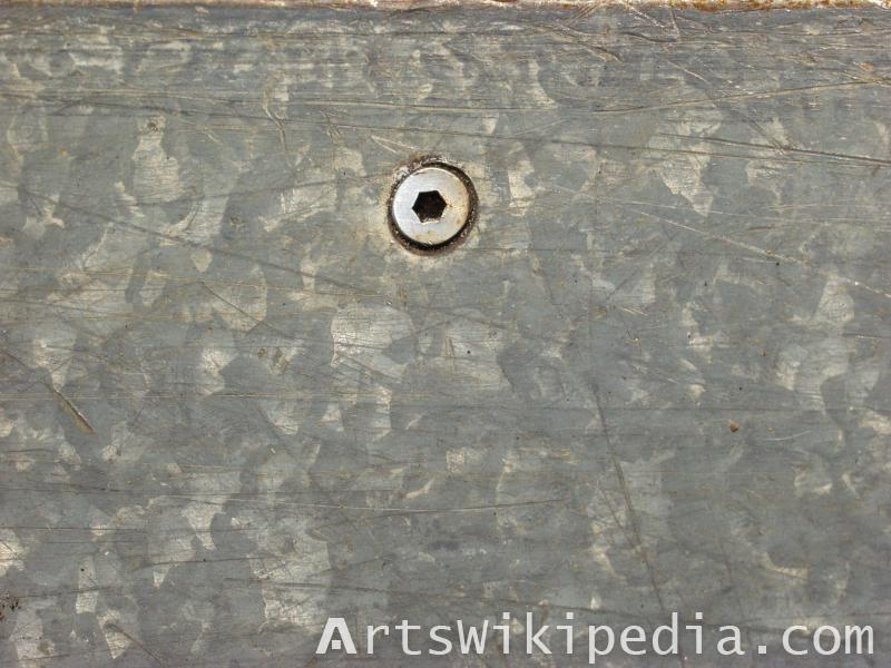 screw and bolt on scratched metal plate