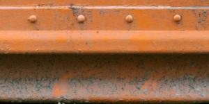 rusty orange painted metal with studs