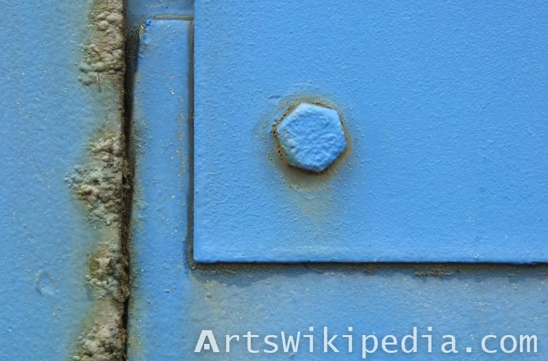 Blue painted bolt on metal plate